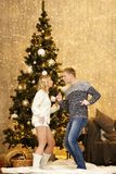 Happy young couple dancing by the Christmas tree Royalty Free Stock Photography