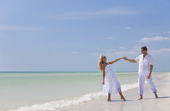 Happy Young Couple Dancing Holding Hands on Beach stock images