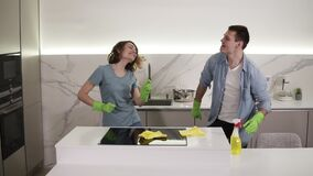 Happy young couple dancing in kitchen both in green rubber gloves having fun on clean-up day in studio apartment. Modern