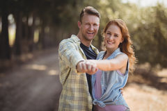 Happy young couple dancing at olive farm during sunny day. Portrait of happy young couple dancing at olive farm during sunny day Stock Images