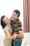 Happy young couple dancing with red rose at home Stock Image