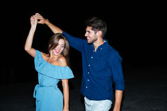 Happy young couple dancing together. At night stock photo