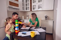 Happy couple with daughter working from home using laptop stock photography