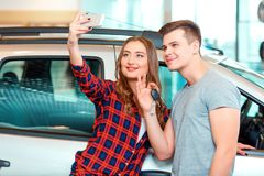 Happy young couple in dealership Royalty Free Stock Photos