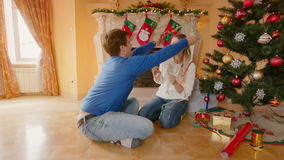 Happy young couple decorating Christmas tree and throwing tinsel at each other stock video footage