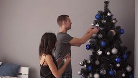 Happy young couple decorating Christmas tree. Young family decorating Christmas tree. Modern, loft interior room. Loving stock footage