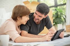 Couple with digital tablet and blueprints planning their new moving house. Happy young couple with digital tablet and blueprints planning their new moving house royalty free stock image