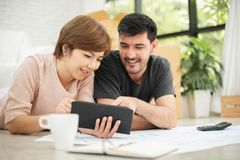Couple with digital tablet and blueprints planning their new moving house. Happy young couple with digital tablet and blueprints planning their new moving house royalty free stock photography