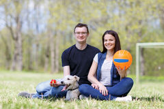 Happy young couple and  dog. Happy young couple and their dog at the park Stock Photos