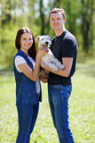 Happy young couple and  dog. Happy young couple and their dog at the park Royalty Free Stock Photos