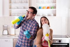 Couple singing and doing chores. Happy young couple doing chores, singing and having fun royalty free stock photos