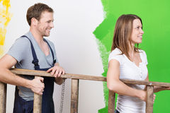 Happy young couple doing home redecorating. Carrying a wooden stepladder together as they paint the walls green Royalty Free Stock Images