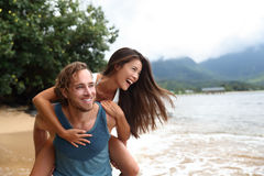 Happy young couple doing piggyback on beach travel. Two young people playing having fun laughing in love. Interracial couple piggybacking, boyfriend carrying royalty free stock image