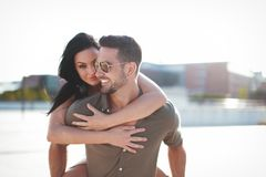 Happy young couple doing piggyback at outdoors woman hiding stock photo