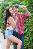 Happy young couple doing selfie by smart mobile phone in the city. Royalty Free Stock Images