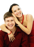 Happy young couple dressed in red. Happy beautiful young couple dressed in red embrace and laugh Stock Image