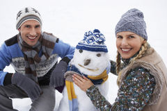 Happy Young Couple Dressing Snowman Stock Photo