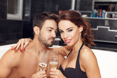 Happy young couple drink champagne in jacuzzi Royalty Free Stock Photography