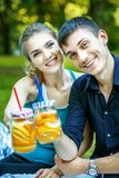 Happy young couple drink detox water with orange and lemon. The. Concept is healthy food, lifestyle and summer royalty free stock images