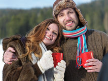 Happy young couple drink warm tea at winter Stock Photos