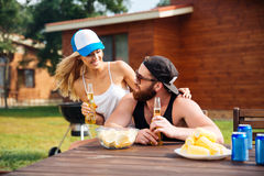 Happy young couple drinking beer outdoors together Stock Photos