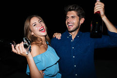 Happy young couple drinking champagne and laughing at night royalty free stock image