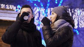 Happy young couple drinking coffee on the Xmas fair. Beautiful family chilling. Merry Christmas and Happy New Year. Concept stock video footage