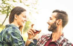 Happy young couple drinking red wine at vineyard farmhouse. Young men looking at beautiful women eyes - People relationship concept with boyfriend and royalty free stock photography