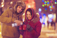 Happy young couple drinking tea on blurred lights background Royalty Free Stock Photography