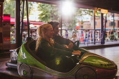 Happy young couple driving a bumper car at amusement park Stock Photos