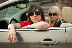 Happy young couple driving convertible car Royalty Free Stock Photos