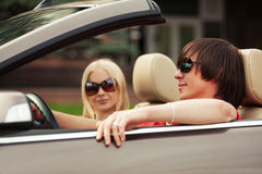 Happy young couple driving convertible car Stock Photos