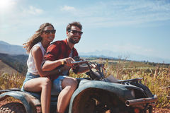 Happy young couple driving a quad bike Stock Photography