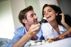 Happy young couple eat breakfast in bed in morning royalty free stock photo