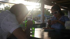 Happy young couple eating meal drinks beer clinking bottles through the sun with lens flare effects in cafe while sun is. Happy young couple eating meal drinks stock video footage