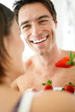 Happy young couple eating strawberries together Royalty Free Stock Images