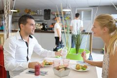 Happy young couple eating together in restaurant royalty free stock photos