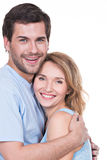 Happy young couple in embrace. Portrait of happy young couple in embrace standing on white background Stock Images