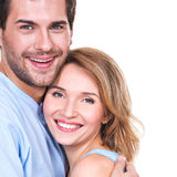 Happy young couple in embrace. Portrait of happy young couple in embrace standing on white background Stock Photography
