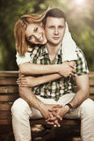 Happy young couple embrace and smiling sitting in the park. Royalty Free Stock Photography