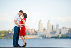 Happy young couple embraces against the city stock image