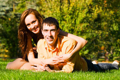The happy young couple embraces on grass Stock Photo