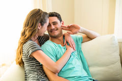 Happy young couple embracing on sofa Royalty Free Stock Photo