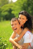 Happy young couple enjoying backriding outdoors Stock Images