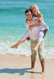 Happy young couple enjoying at beach royalty free stock images
