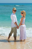 Happy young couple enjoying at beach stock photography