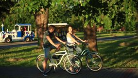Happy young couple enjoying bicycle ride. Sunny summer time. Happy young couple enjoying bicycle ride stock footage