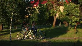 Happy young couple enjoying bicycle ride. Sunny summer time. Happy young couple enjoying bicycle ride stock video footage