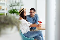 Happy young couple enjoying a glass of red wine after shopping stock photo