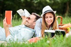 Happy young couple enjoying a good read during picnic in a park. Man is lying with his head resting on girlfriend`s back royalty free stock images